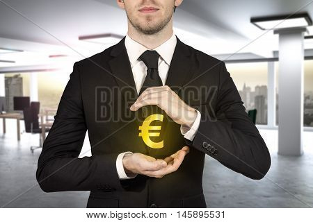 businessman in modern office protecting golden euro symbol