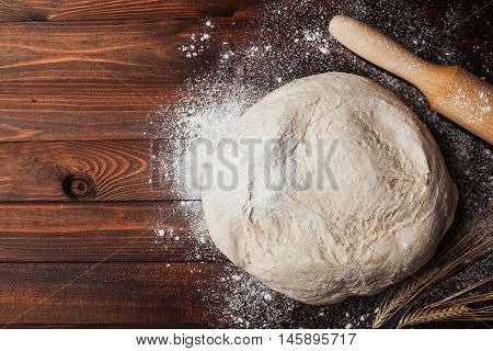 Dough with flour rolling pin and wheat ears on rustic wooden table from above. Homemade pastry for bread or pizza. Bakery background.