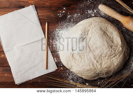 Dough with flour baking paper rolling pin and wheat ears on rustic wooden table top view. Homemade pastry for bread or pizza. Bakery background.