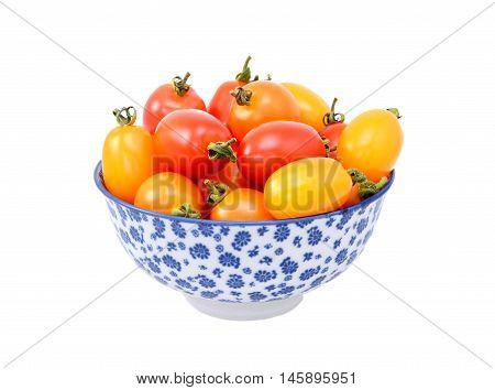Mixed red and yellow cherry plum tomatoes in a blue and white porcelain bowl with a floral design isolated on a white background
