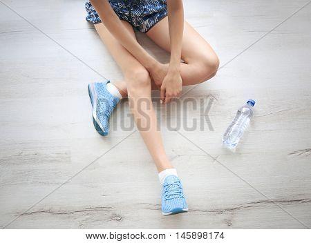 Woman wearing mint sneakers on wooden floor background