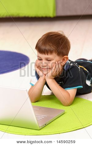 Happy little boy (5 years) lying on floor at home using laptop computer.?