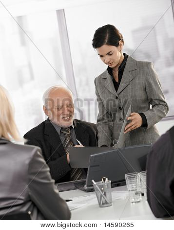 Mid-adult assistant holding documents to sign for senior executive at business meeting.?