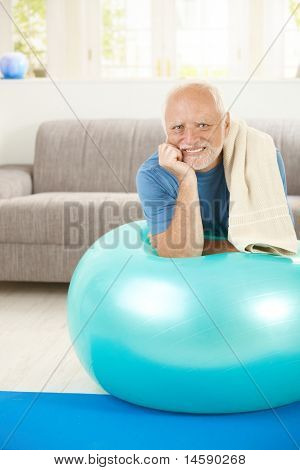 Portrait of sporty senior man with exercise ball, looking at camera, smiling.?
