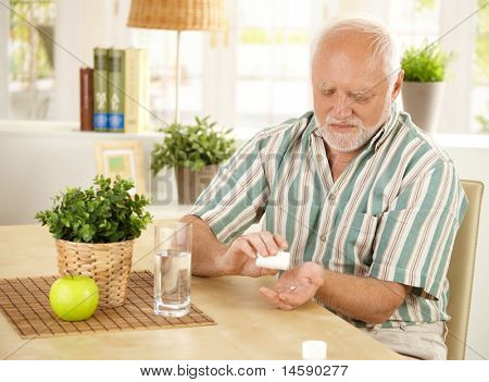 Elderly man taking pill at home, sitting at living room table.?