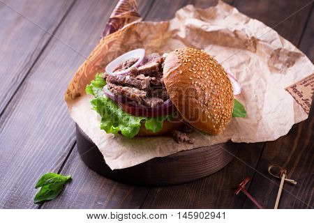 Delicious beef burger with salad ingredients served on a craft paper on a rustic wooden table. Sloppy joe burger with sliced meat.