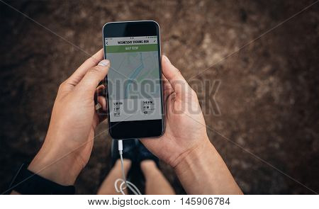 Close up shot of female checking the summary of her run on mobile phone. Woman runner using a fitness app on her smartphone. POV shot with focus on cellphone in hands.