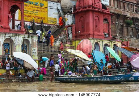 VARANASI, INDIA - AUGUST 17, 2015: People bathing and washing clothes in the holy water of the Ganges river at one of the many ghats along the bank of the Ganges.
