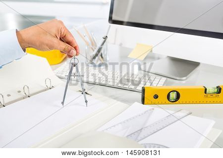 Close-up Of Architect Hands Using Metal Drawing Compass