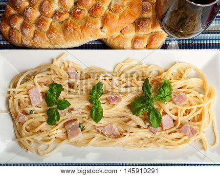 Spaghetti carbonara decorated with fresh basil leaves. Bread and red win on background