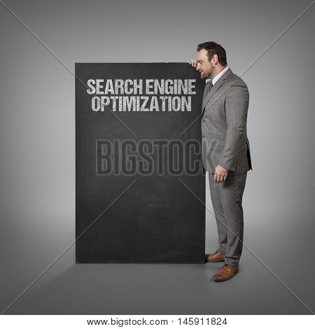 Search engine optimization text on blackboard with businessman standing side