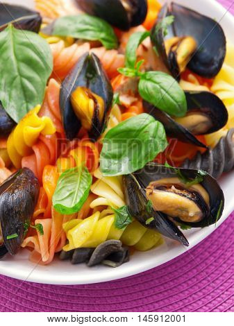 Colorful fusilli pasta with clams and basil. Vertical shot.
