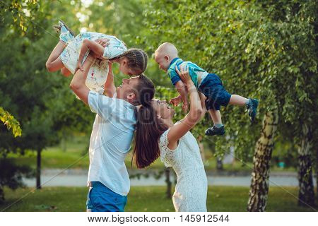 Young family of four having fun in the park