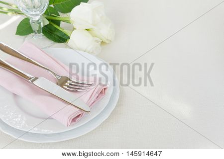 Beautiful decorated table with white plates crystal glass linen pink napkin cutlery and white rose flowers on tablecloths with space for text