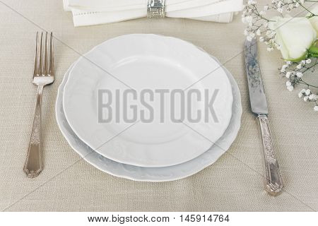 Beautiful decorated table with empty white plates linen napkin cutlery and white rose flowers on tablecloths with space for text