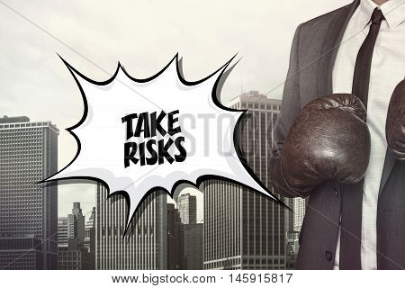 Take risks text on speech bubble with businessman wearing boxing gloves