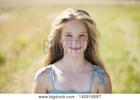 Portrait of a beautiful blonde little girl on the background of wheat field