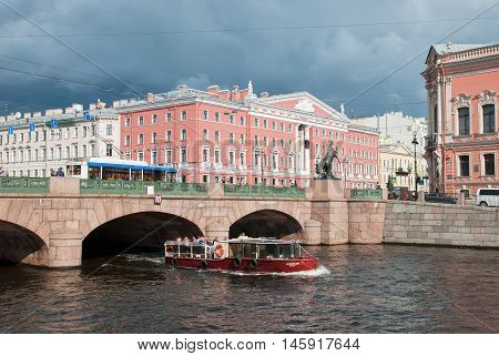 SAINT - PETERSBURG, RUSSIA - SEPTEMBER 5, 2016: People in the tourist boat sail on the Fontanka River under The Anichkov Bridge with The Horse Tamers by Peter Klodt near Nevsky Avenue