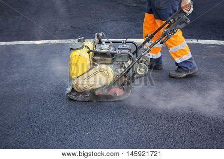 Worker use vibratory plate compactor compacting asphalt at road repair