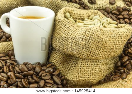 fresh espresso and green coffee in small jute bag at strewn mediumly roasted coffee beans