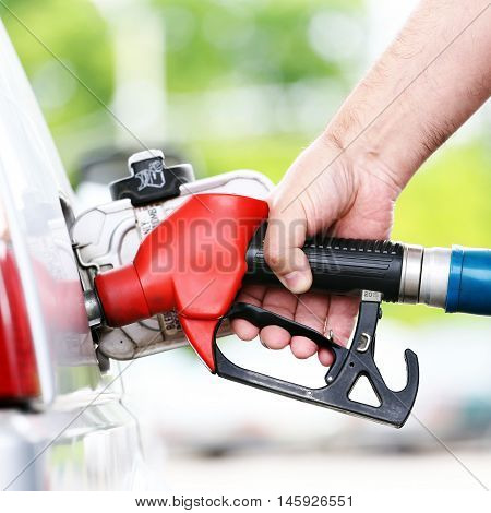 Refuel car with a petrol nozzle on a refuel station