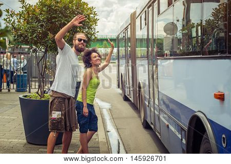 Young Couple Waving Goodbye To Their Friends On The Bus