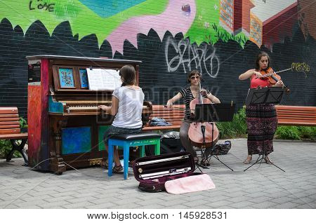MONTREAL CANADA JUNE 22 2016: Street musicians playing outdoors at free piano in Montreal