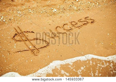 Word Success written in the sand on the beach