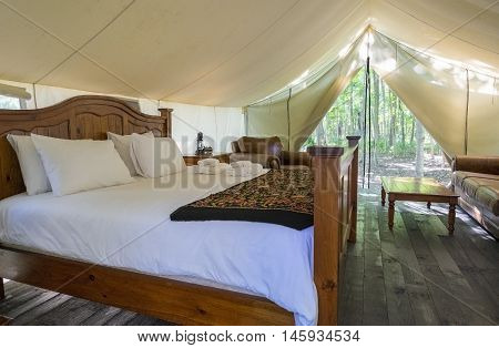 Interior of a Luxury Camping Tent with King Size Bed and Leather Furniture