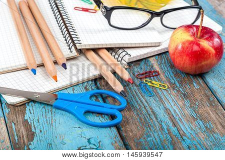 Notepad pencils scissors paper clips and glasses. Office or school supplies on wooden planks painted in blue.