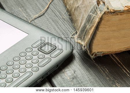 Old book and grey eReader on the dark table