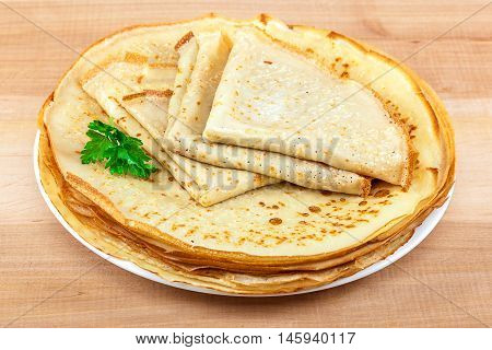 Pancakes in the plate on a wooden background.