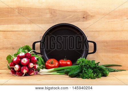 Fresh vegetables and pan on a wooden background.