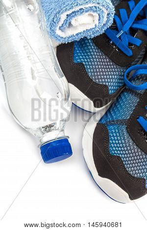 Sport shoes towels and water bottle isolated on a white background.