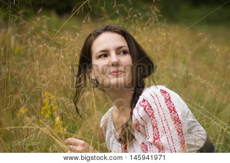 Portrait of a beautiful smiling young girl in nature wearing embroidered top