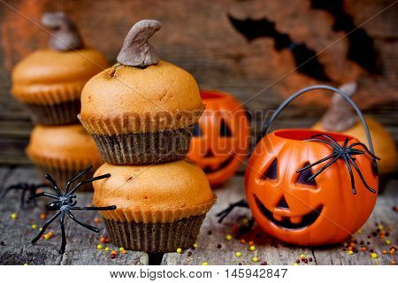 Homemade Halloween pumpkin cupcakes on dark wooden background for trick or treat night. Festive Halloween party background selective focus