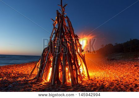 A big fireplace set on fire at the beach