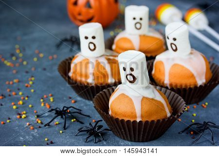 Delicious Halloween treat for dessert pumpkin chocolate muffins with sweet white marshmallow ghosts selective focus