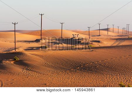 Uneven Row of Electricity Pylons Stretching Across the Early Morning Shifting Sands of the Desert