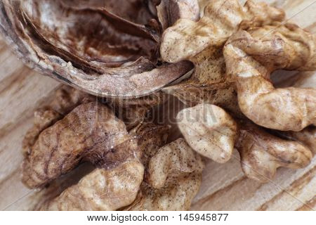 Walnut and nutshell on wooden table taken closeup.