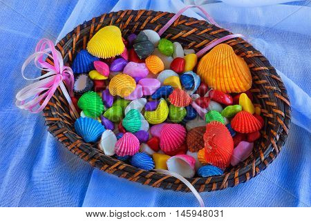 Colorful seashells and peebles in a straw basket as a decoration on the table