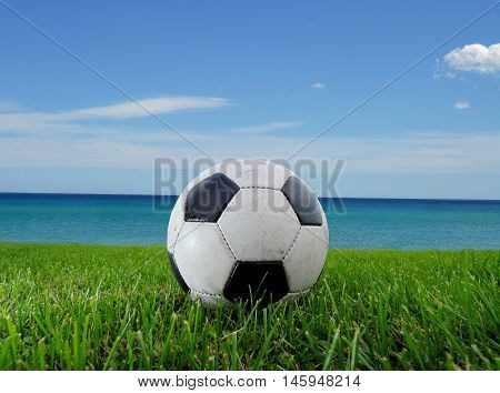 Football on the grass in the summer and the sea