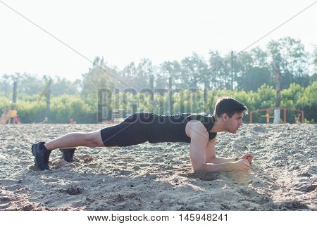 Fit man doing pank exercise during training workout on beach in summer