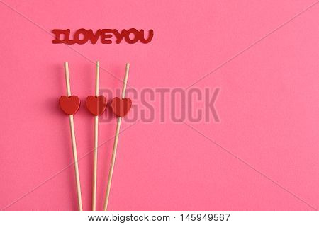 Valentine's Day. Three red hearts on sticks with a pink background an I love you in red lettering