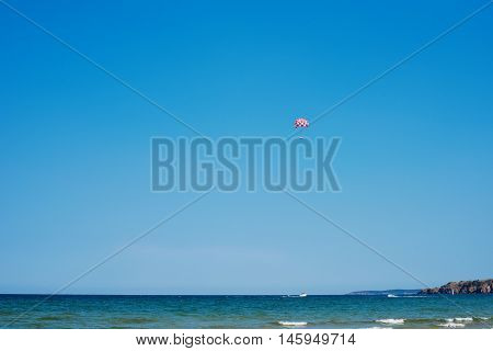 Parachuting Over A Sea, Towing By A Boat. Paragliding In The Clear Sky Above The Sea. Riding On A Pa