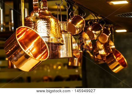 Copper kitchenware (pots pans jugs) hang from the ceiling in the kitchen.