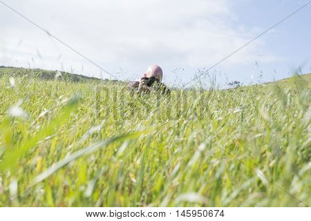 Stalking middle aged bald male photographer hiding in the long grass and taking a picture.