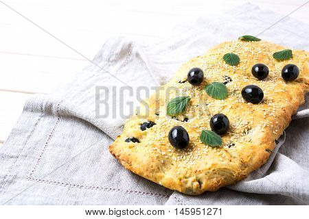 Fresh Italian focaccia with olive garlic and herbs. Homemade traditional Italian bread on the linen napkin.