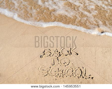 Finger drawn Back to School writing on beach sand