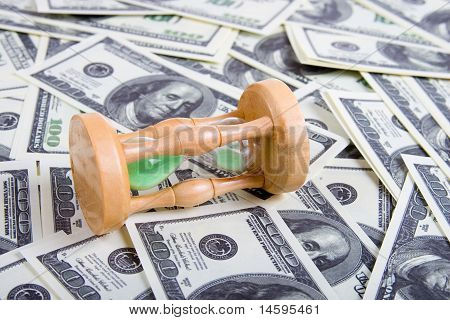 Sandglass On A Stack Of Dollars
